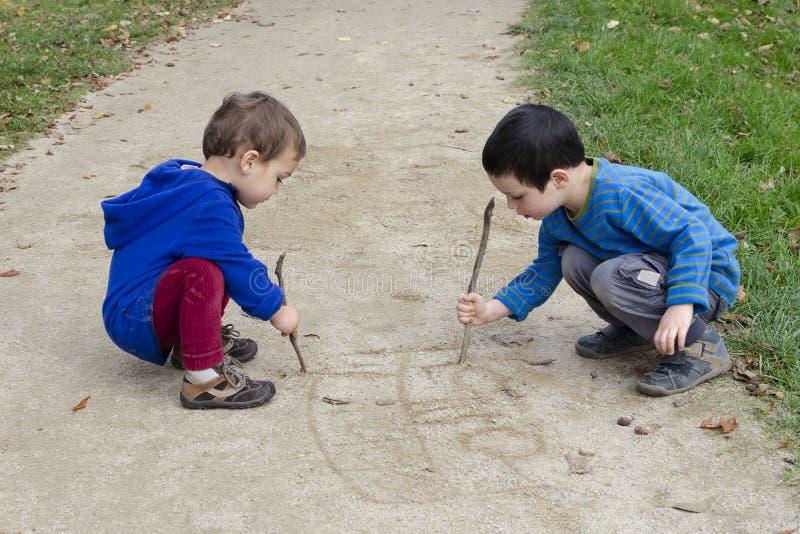 Kinder, die in Sand zeichnen stockfotografie
