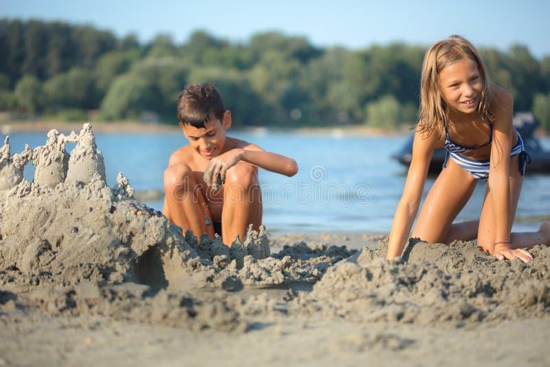 Kinder, die Sandburg am tropischen Strand machen stockbild