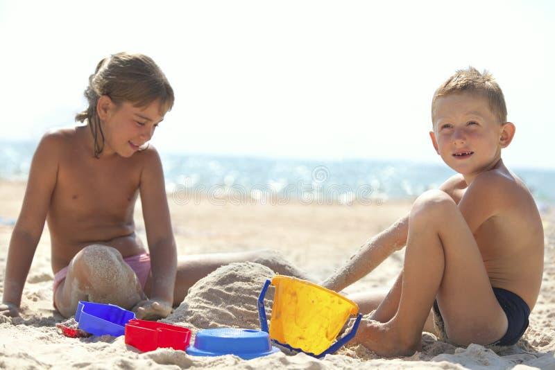 Kinder, die Sandschloß auf Strand aufbauen stockbilder