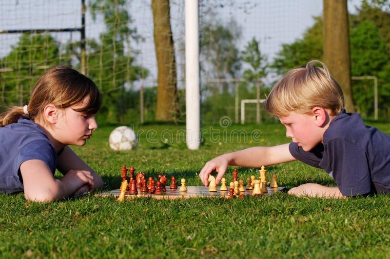 Kinder, die Schach auf einem Fußballplatz spielen lizenzfreie stockfotos