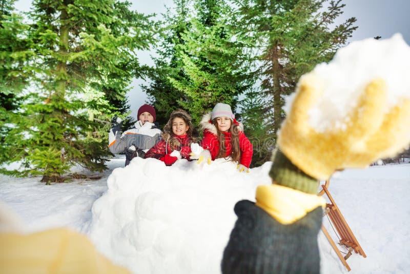 Kinder, die Schneebälle am Winterwald spielen stockfotografie