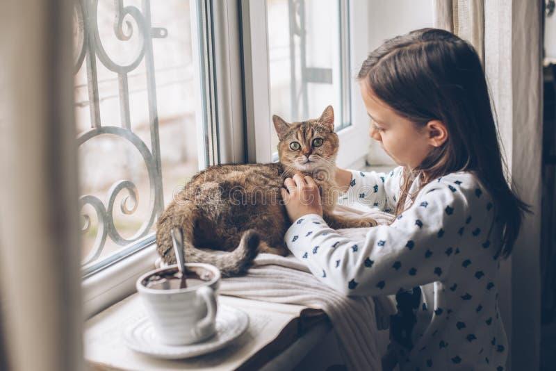 Kinder, die sich mit einer Katze auf einer Fensterbank entspannen lizenzfreie stockfotografie