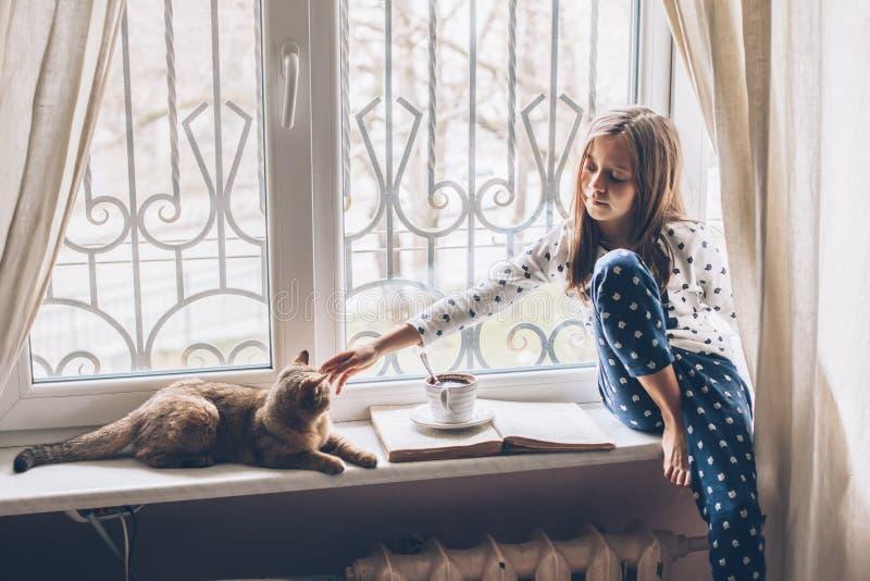 Kinder, die sich mit einer Katze auf einer Fensterbank entspannen stockbild