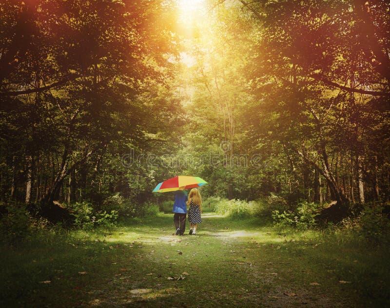 Kinder, die in Sonnenschein-Holz mit Regenschirm gehen lizenzfreie stockbilder