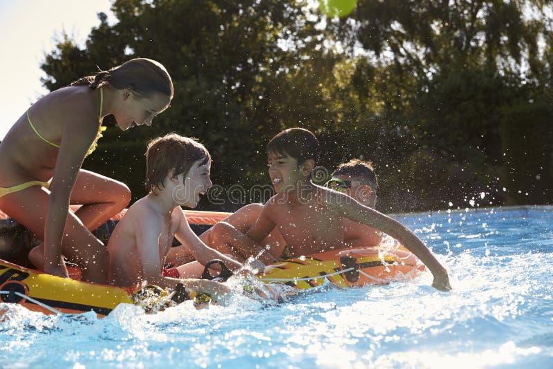 Kinder, die Spaß auf aufblasbarem Swimmingpool im im Freien haben stockfotografie