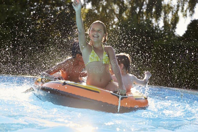 Kinder, die Spaß auf aufblasbarem Swimmingpool im im Freien haben lizenzfreie stockbilder