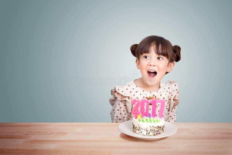 Kinder, die Spaß an der Partei des neuen Jahres mit Kuchen und Kerze 2017 haben stockfotografie