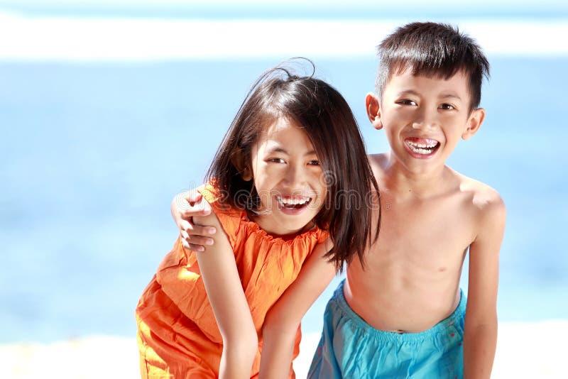 Kinder, die Spaß im Strand haben stockfotos