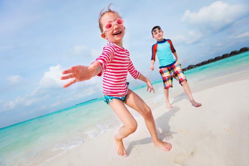 Kinder, die Spaß am Strand haben stockfotografie