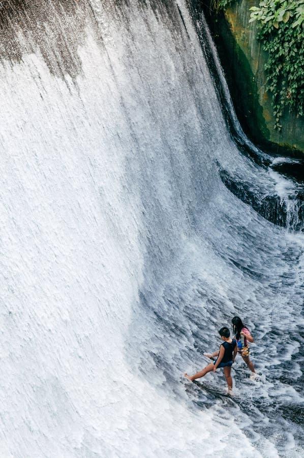 Kinder, die Spaß an Wasserfalllandhaus escudero, San Pablo, Philippinen haben lizenzfreie stockfotos