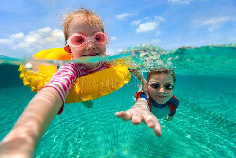 Kinder, die Spaßschwimmen auf Sommerferien haben stockbild