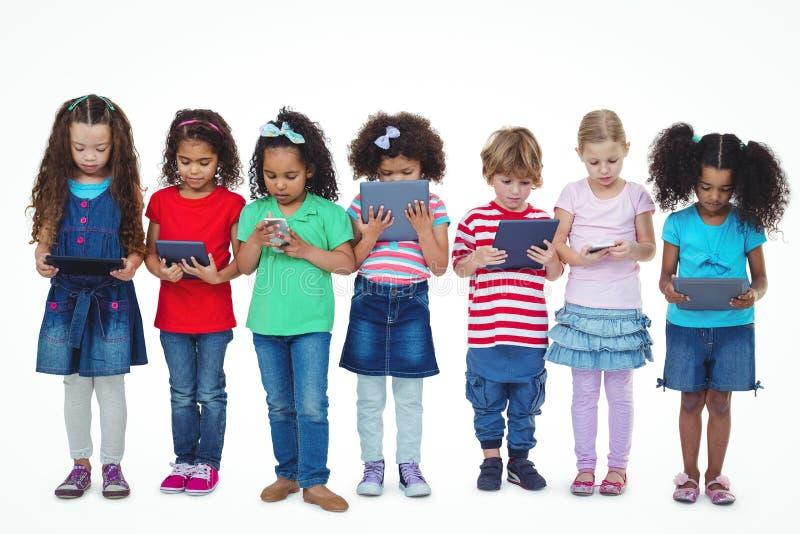 Kinder, die stehen, zusammenhalten Tabletten und Telefone lizenzfreie stockfotografie