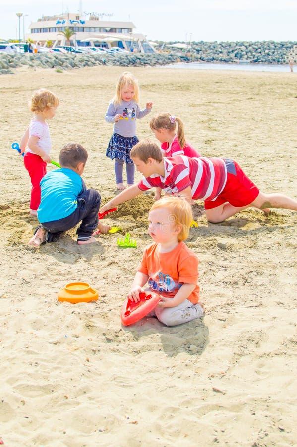 Kinder, die am Strand spielen stockbild
