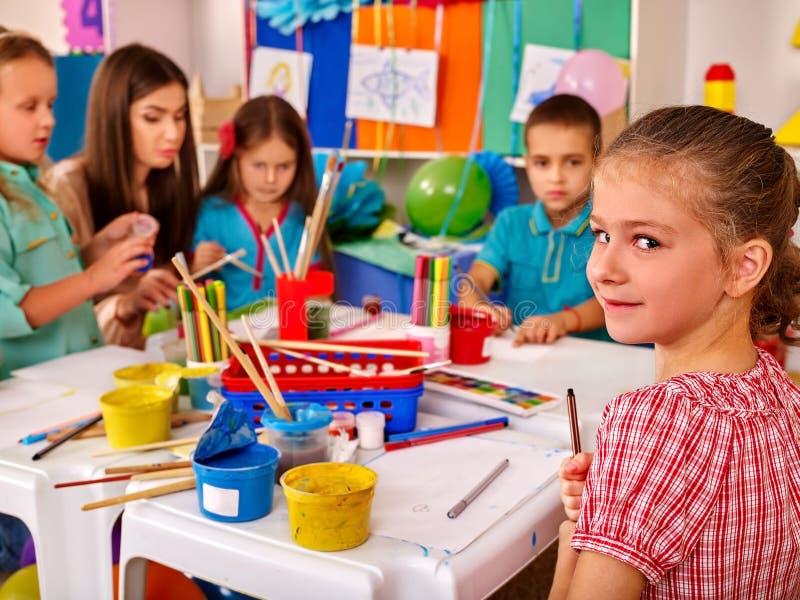 Kinder, die an Tabelle im Kindergarten halten stockbilder