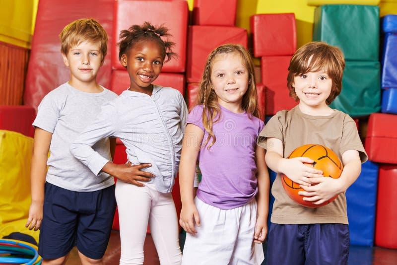 Kinder, die Team für Ballspiel in der Turnhalle bilden stockbild