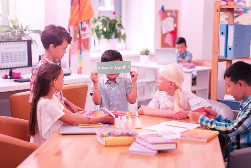 Kinder, die am Tisch in der Schule sitzen stockbilder