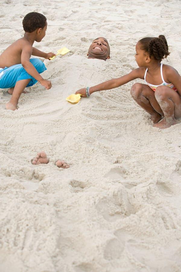 Kinder, die Vater im Sand begraben lizenzfreie stockfotografie