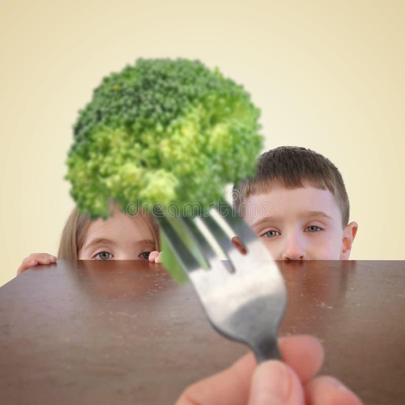 Kinder, die vom gesunden Brokkoli-Lebensmittel sich verstecken stockbilder