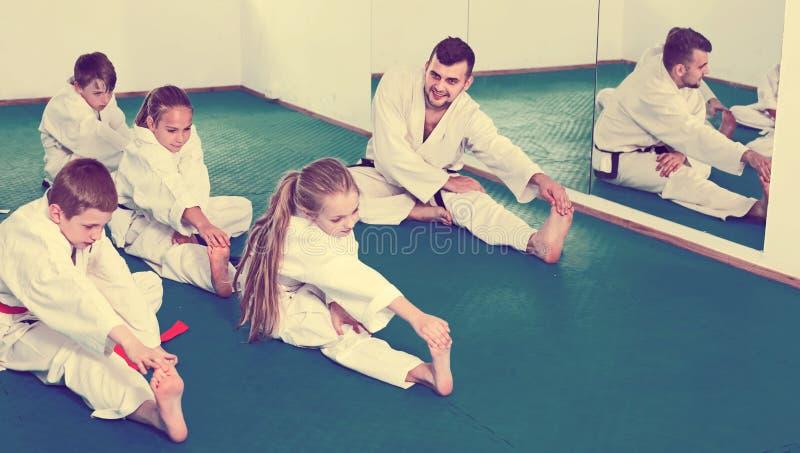 Kinder, die vor Karateklasse ausdehnen stockbild
