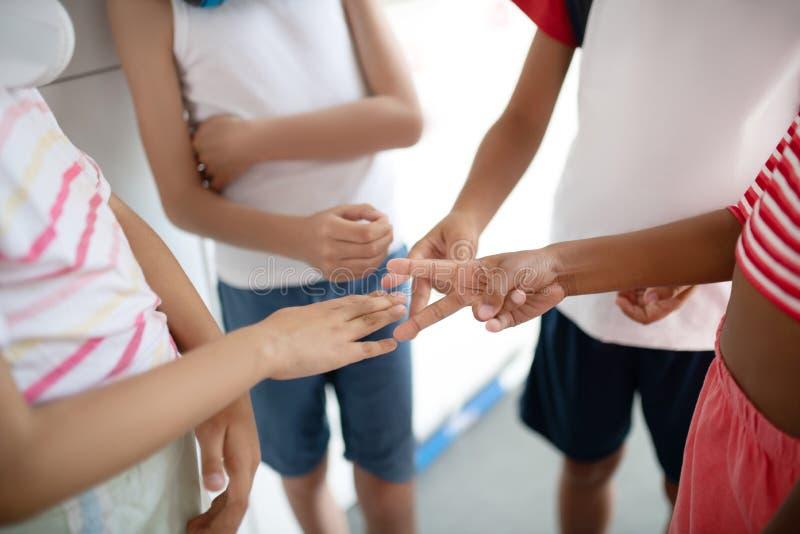 Kinder, die während der Kontroverse Rockpapier-Schere spielen lizenzfreie stockfotos