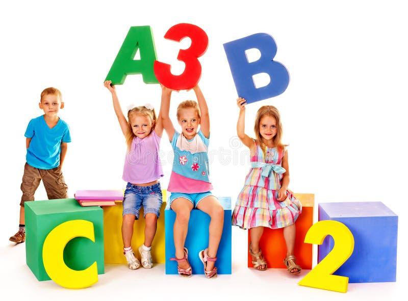 Kinder, die am Würfel sitzen stockfoto