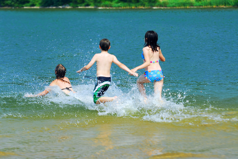 Kinder, die in Wasser laufen stockbilder