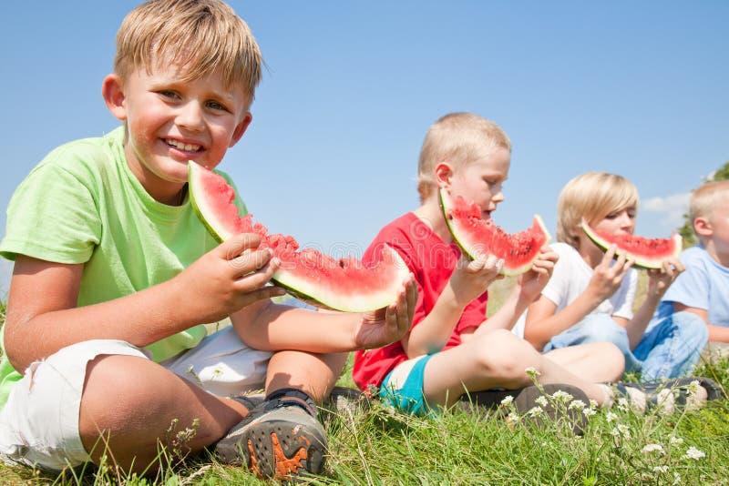 Kinder, die Wassermelone essen stockfotografie