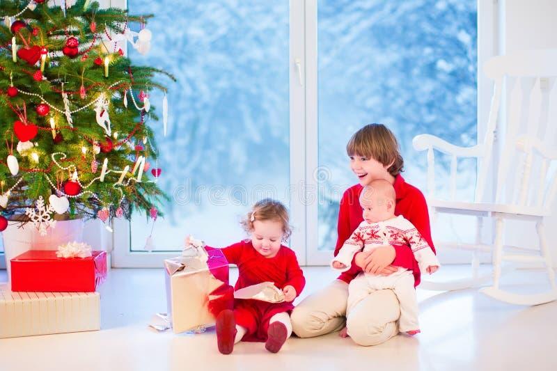 Kinder, die Weihnachtsgeschenke öffnen lizenzfreie stockbilder