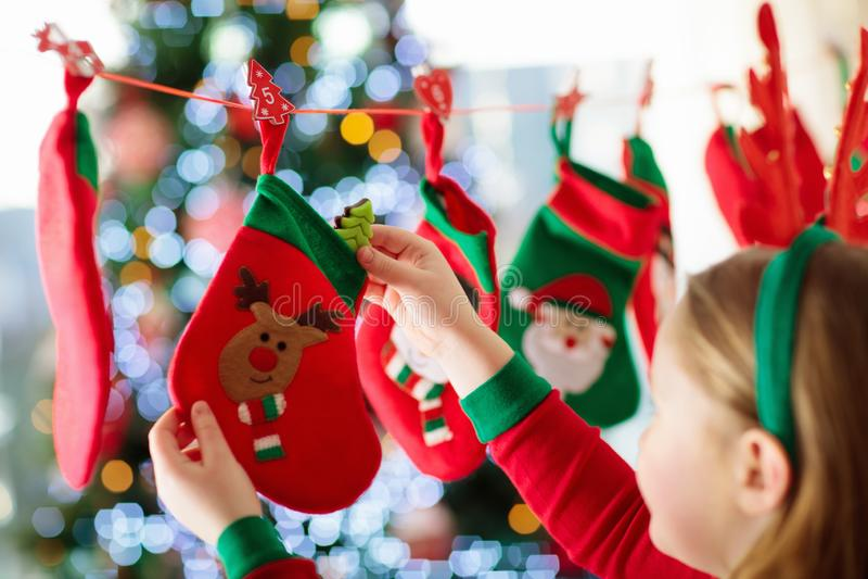 Kinder, die Weihnachtsgeschenke öffnen Kind, das nach Süßigkeit und Geschenken im Einführungskalender auf Wintermorgen sucht Verz lizenzfreie stockfotos