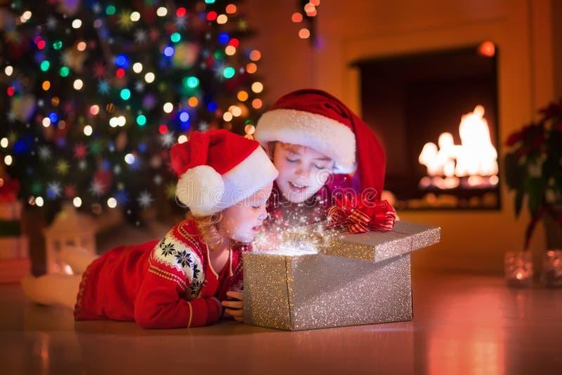 Kinder, die Weihnachtsgeschenke am Kamin öffnen stockfotos