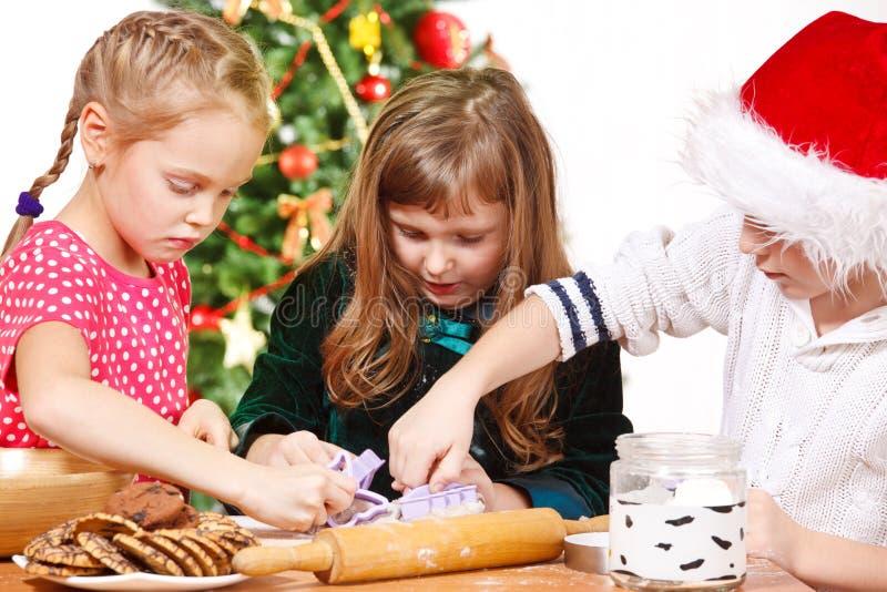 Kinder, die Weihnachtsplätzchen schneiden lizenzfreie stockfotos