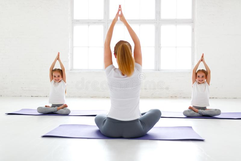 Kinder, die Yoga in einer Lotoshaltung mit Lehrer üben stockbilder