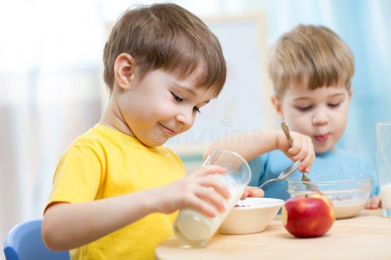 Kinder, die zu Hause gesundes Lebensmittel essen stockfotografie