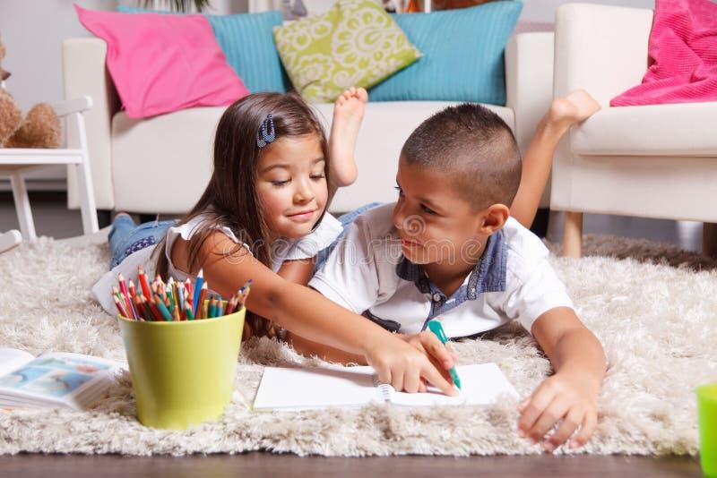 Kinder, die zu Hause Hausarbeit tun stockbild