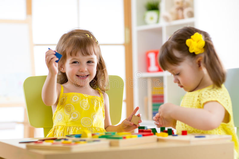 Kinder, die zu Hause mit Entwicklungsspielwaren oder Kindergarten oder playschool spielen stockfotografie