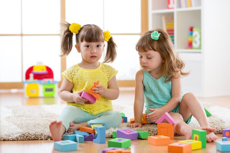 Kinder, die zu Hause mit Entwicklungsspielwaren oder Kindergarten oder playschool spielen lizenzfreie stockfotos