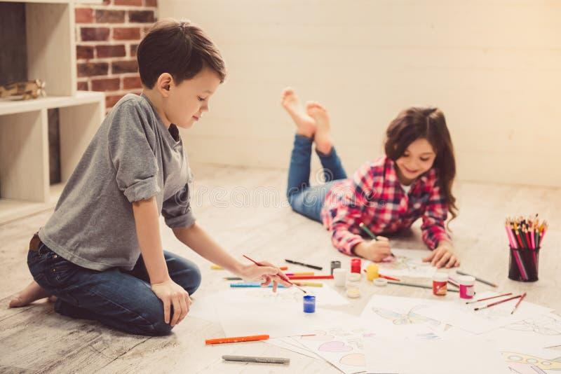 Kinder, die zu Hause zeichnen stockbilder