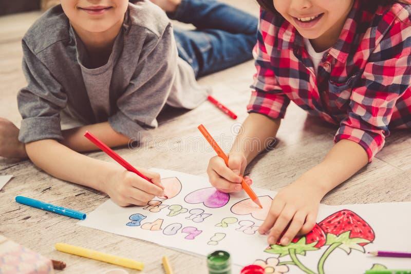 Kinder, die zu Hause zeichnen stockbild