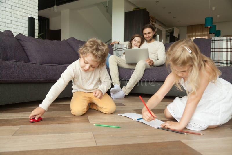 Kinder, die zu Hause zeichnen, Familienausgaben-Freizeit toget spielen lizenzfreies stockfoto