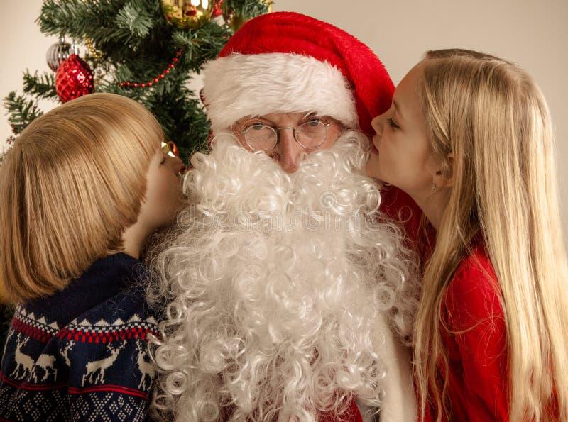 Kinder, die zu Santa Claus flüstern lizenzfreie stockfotos