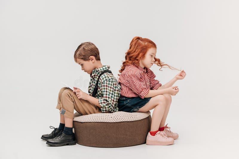 Kinder, die zurück zu Rückseite während Junge verwendet digitale Tablette sitzen lizenzfreie stockbilder