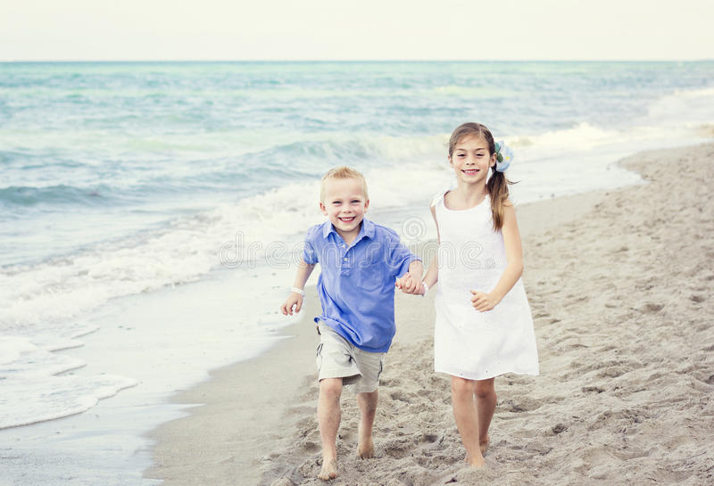 Kinder, die zusammen entlang den Strand laufen lizenzfreie stockbilder