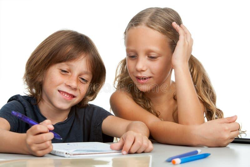 Kinder, die zusammen Heimarbeit tun. stockbilder