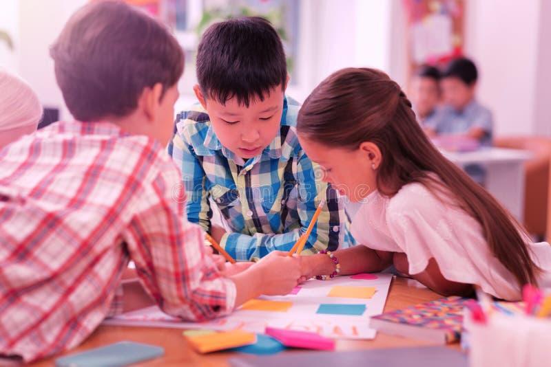 Kinder, die zusammen an ihrem Schulprojekt arbeiten stockbilder