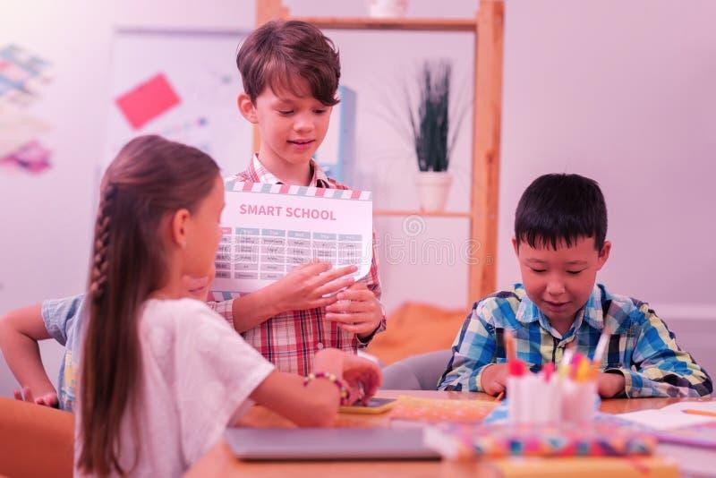 Kinder, die zusammen während des Schulbruches sitzen lizenzfreies stockbild