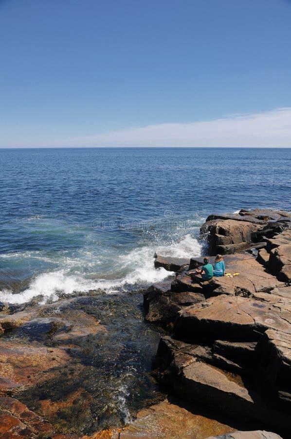Kinder, die zusammenstoßende Wellen aufpassen stockfotografie