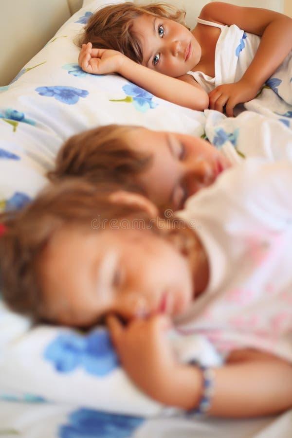 Kinder drei zusammen schlafend auf Bett stockbilder