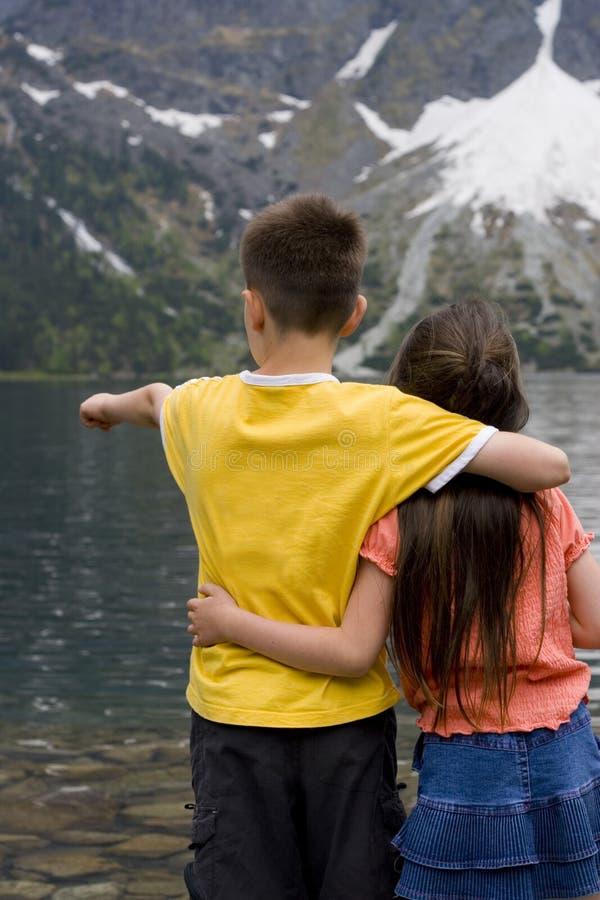Kinder durch einen Mountainsee stockbild