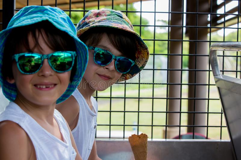 Kinder, Eiscreme essend, beim Sitzen in einem Safari-LKW lizenzfreie stockbilder