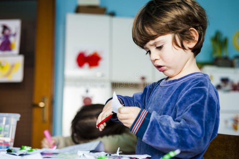 Kinder färben und zeichnen und schneiden die Zeichnungen heraus, die durch sie gemacht werden lizenzfreies stockbild